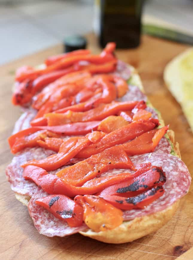 layers of salami and red pepper on foccacia bread