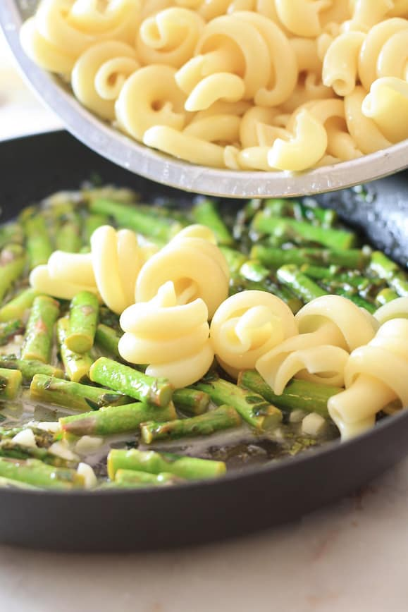 a skillet of asparagus and butter mixture with pasta being poured into it with a silver strainer
