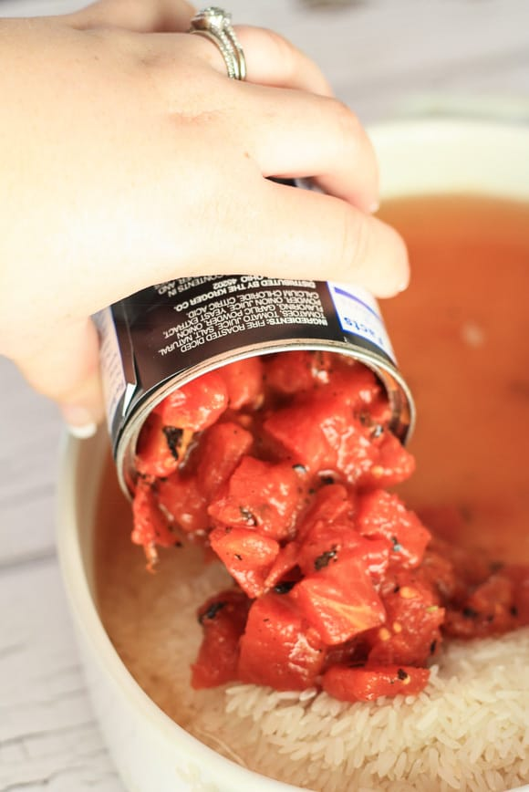 A dish with a can of tomatoes being poured into it