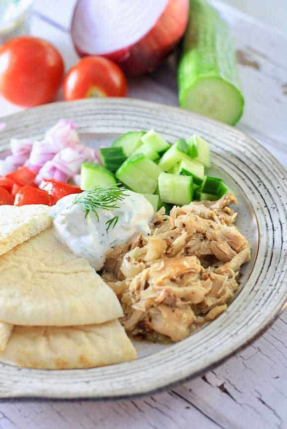 A plate full of greek chicken with pita, cucumber, red onion and tomatoes