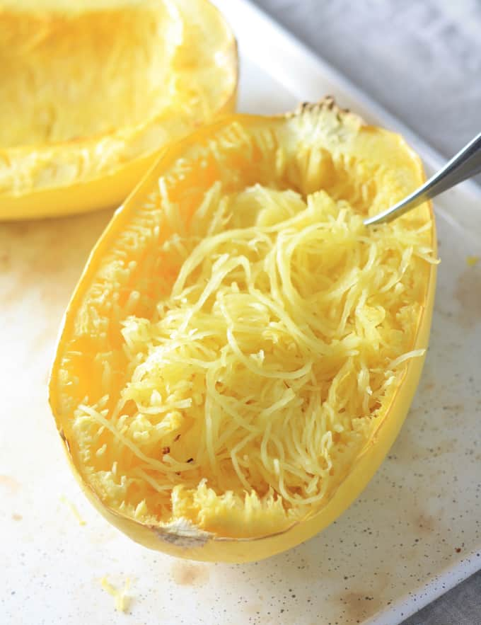 A spaghetti squash cut in half after being baked and shredded with a fork