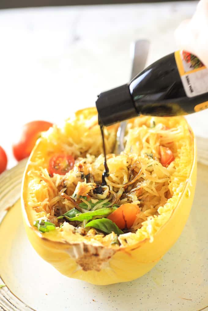 Spaghetti squash being drizzled with balsamic reduction