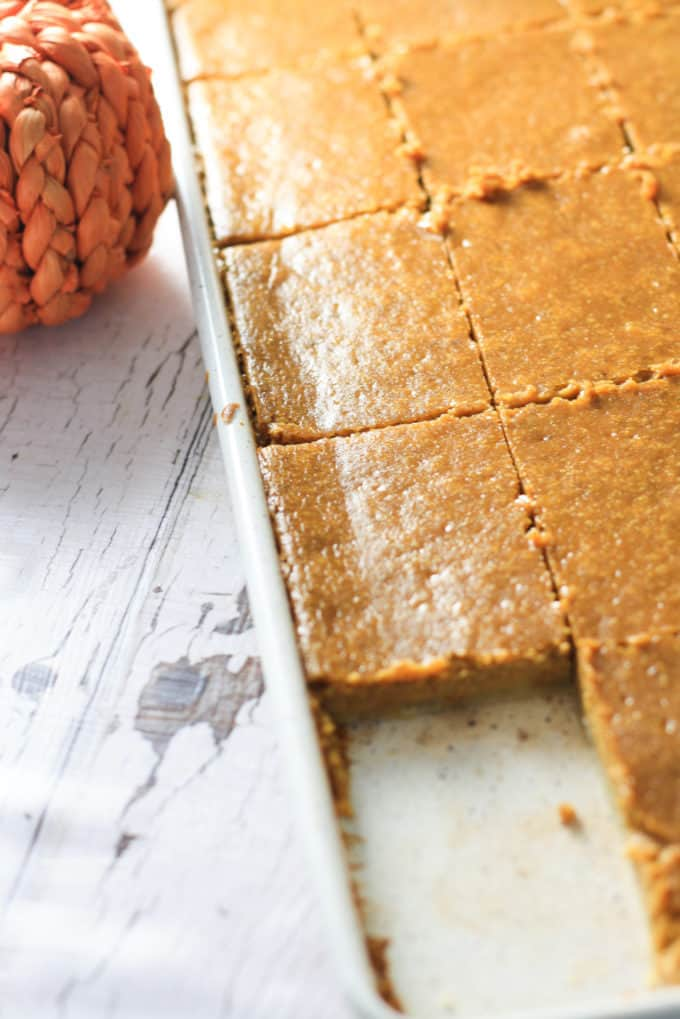 A white sheet pan with pumpkin pie it sliced into squares.