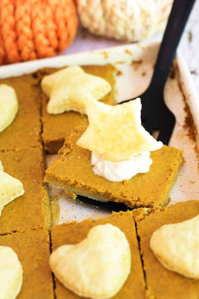 A white sheet pan with pumpkin pie being sliced with a spatula. Each piece has a star pastry puff on it with whipped cream.