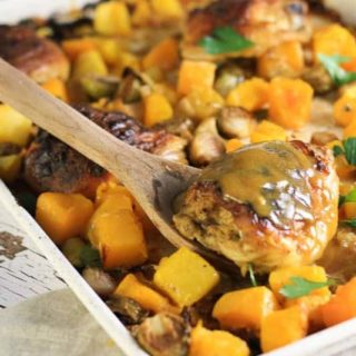 A white sheet pan with roasted chicken thighs and roasted fall vegetables