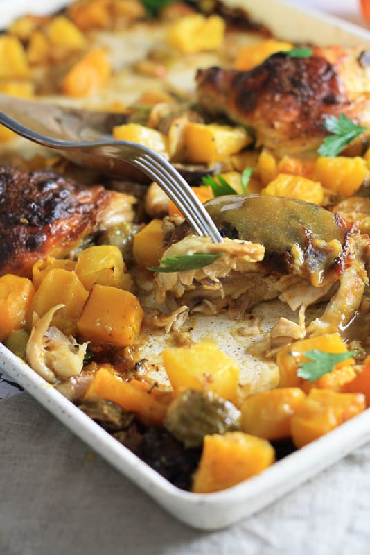 A white sheet pan with roasted butternut squash and chicken; a fork is cutting into the chicken and being lifted by 1/4 inch