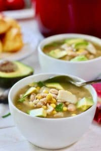 two bowls of white chicken chili with a spoon