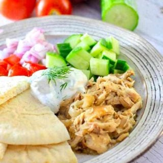 slow cooker greek chicken on a plate with cucumbers, red onion, tomato, pita and Tzatiki
