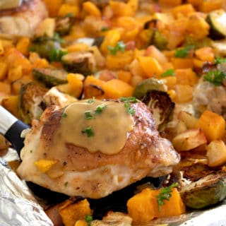 side angled view of chicken with veggies on sheet pan