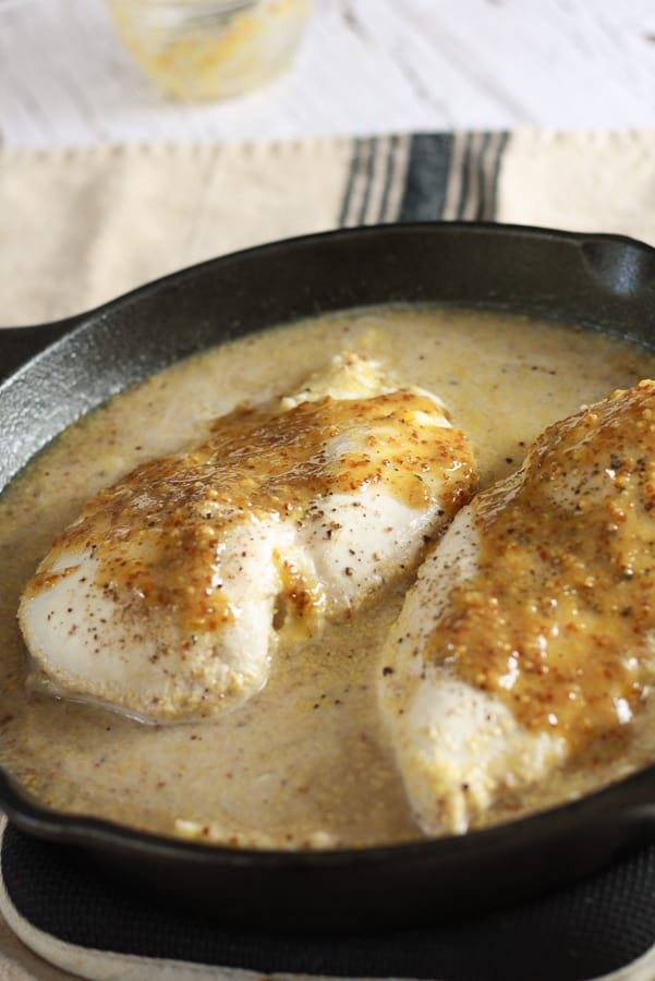 A black cast iron pan with a watery mixture of rice, broth, and 2 chicken breasts slathered in honey mustard sauce