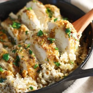 A black cast iron pan with oven baked honey mustard chicken and rice sprinkled with parsley. The chicken has been sliced into 1/2 inch pieces and is resting on top of the rice.