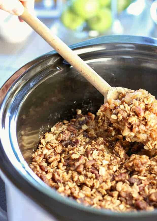 slow cooker apple crisp being served out of the crock pot