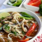 Noodles and broth in a beautiful white bowl topped with veggies for an amazing chicken pho
