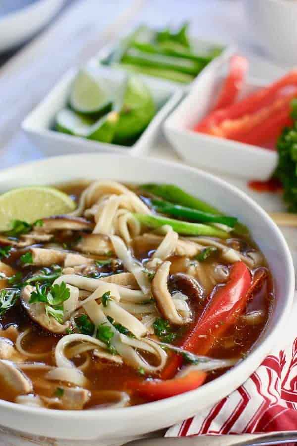 Chicken Pho on a colorful cloth with ingredients for topping