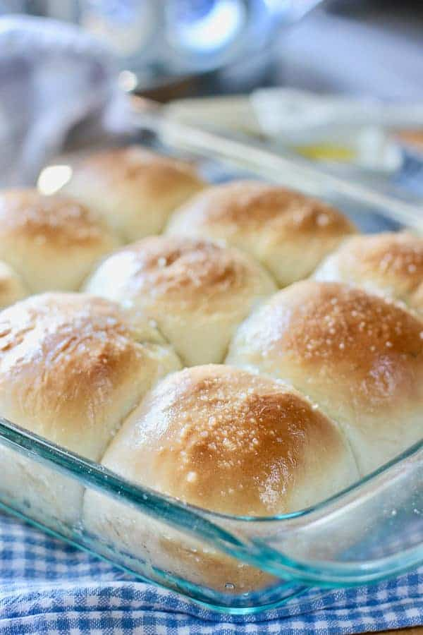 homemade rolls in a glass pan on a checkered cloth