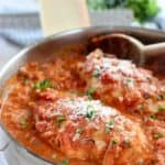 chicken breasts cooking in skillet with tomato sauce