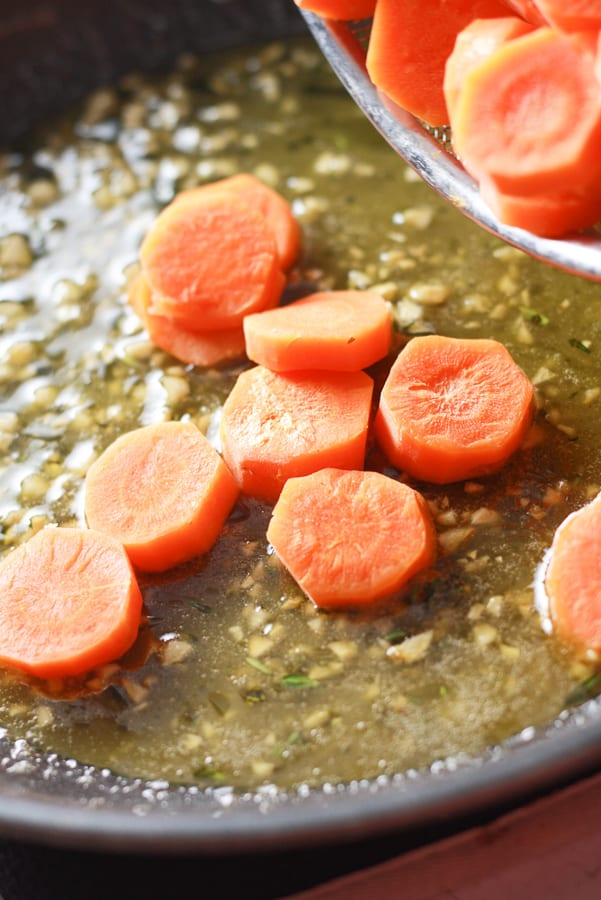 a teflon pan with carrots being poured into it atop a honey butter garlic sauce