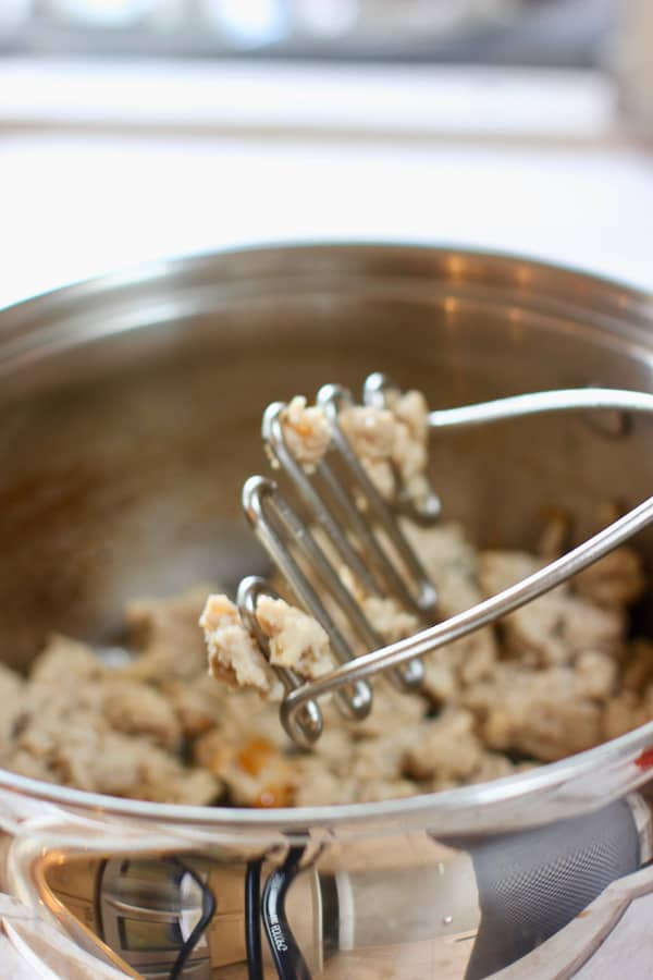 ground turkey being browned in a large pot and stirred with a potato masher