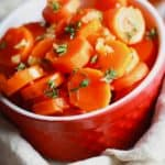 candied carrots in a red bowl with thyme and garlic