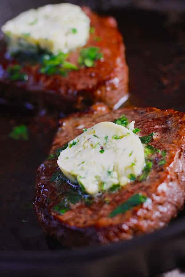 pan seared steak with compound butter and parsley in a black cast iron pan