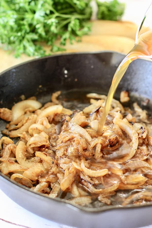 carmalized onions in a cast iron skillet with broth being poured