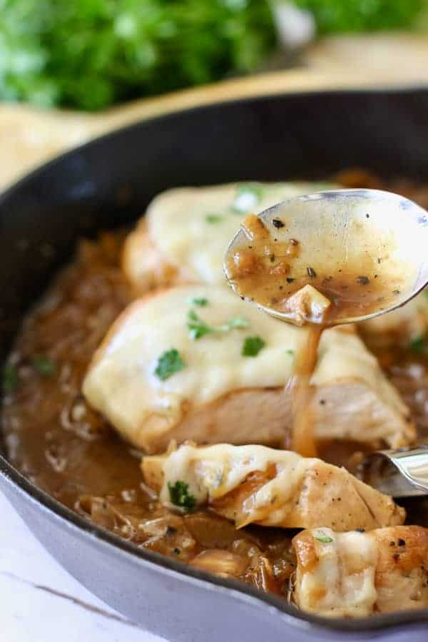 French onion chicken with sauce being poured over it
