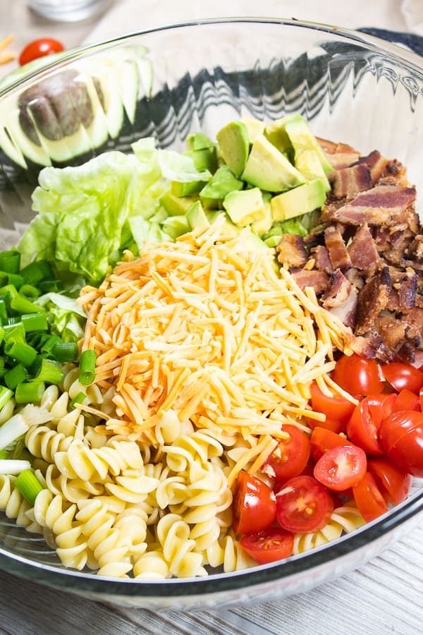 a clear glass bowl with all ingredients of this dish displayed each in its own section; tomato, avocado, green onion, pasta, lettuce, cheddar cheese, tomato and bacon