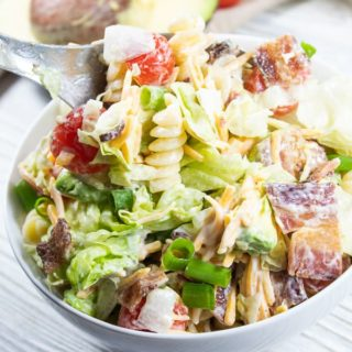 a white bowl on white woodshed boards filled with salad that contains pasta, avocado, tomato, bacon, and salad tossed in ranch