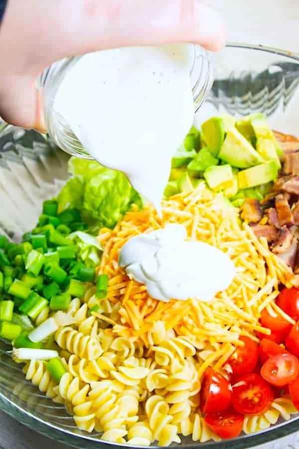 pouring ranh dressing on BLT pasta salad