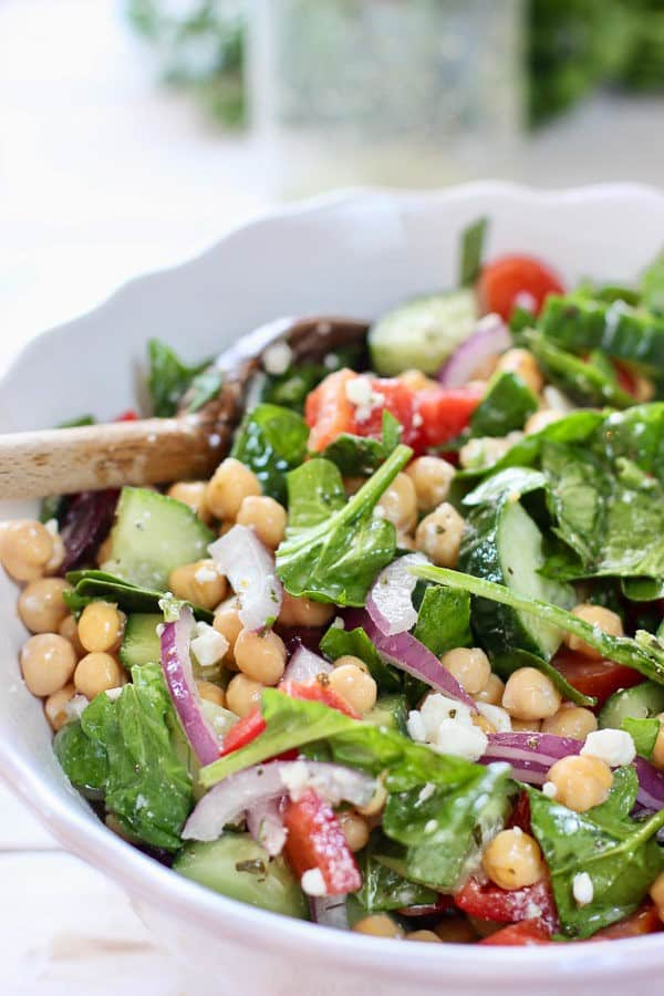 chickpeas, spinach salad in a white bowl