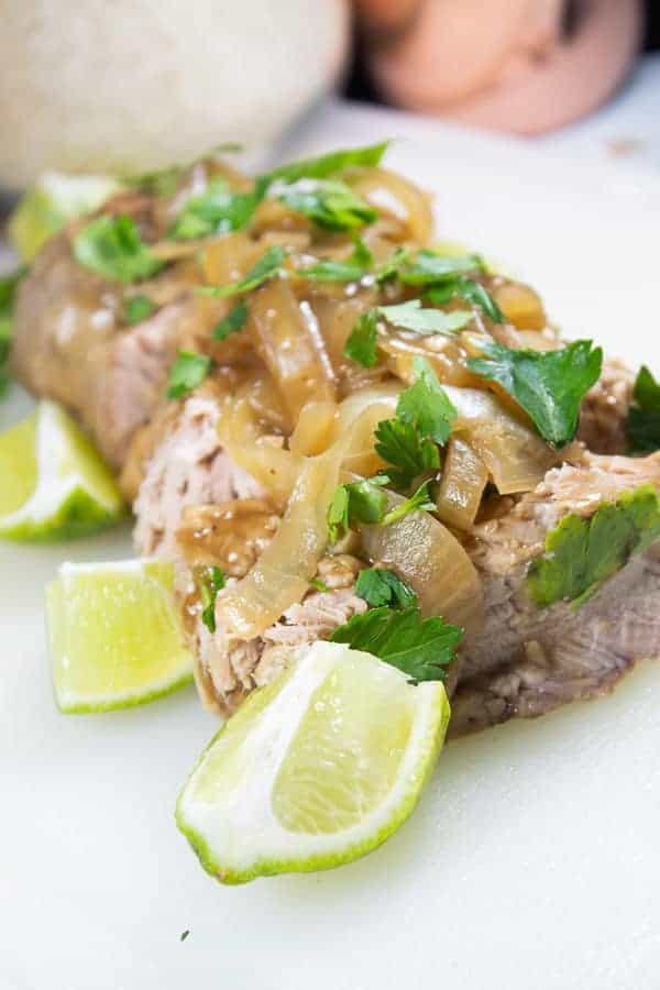 A pork loin on a white platter with slices of braised onion, fresh lime wedges and cilantro