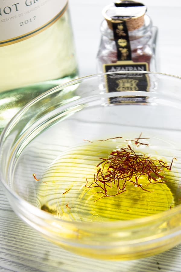 A clear glass bowl full of white wine and saffron threads