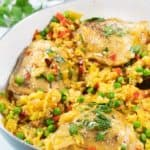a white pan with saffron colored rice and chicken, known as Spanish chicken and rice or arroz con pollo