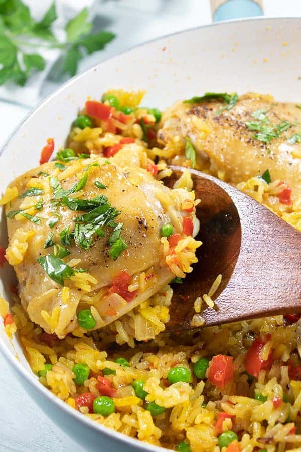 a white pan with a wooden spatula showing Spanish chicken and rice