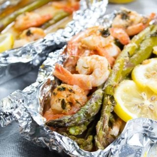 a foil packet filled with shrimp, asparagus and lemon slices