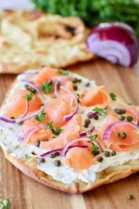 smoked salmon pizza on a board ready to serve