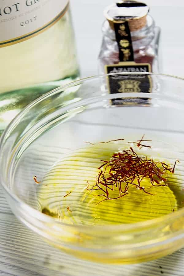 blooming saffron in clear dish of white wine