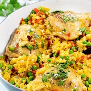 Closeup of Spanish chicken and rice in white pan garnished with parsley