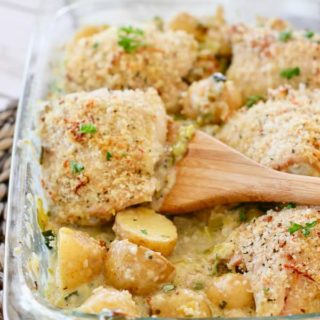 Crispy chicken thighs in a baking dish with potatoes and cream sauce