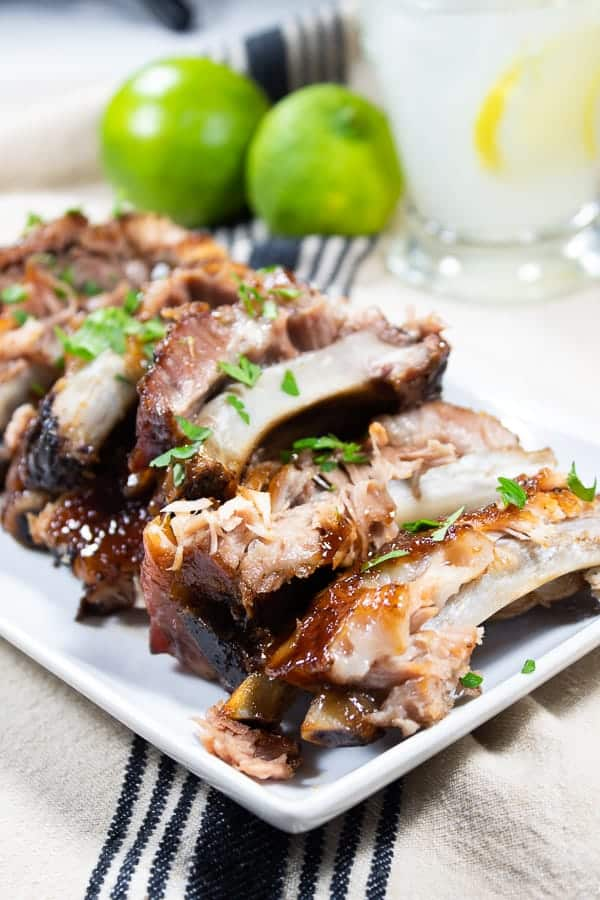 a white platter with tender bbq ribs garnished with parsley