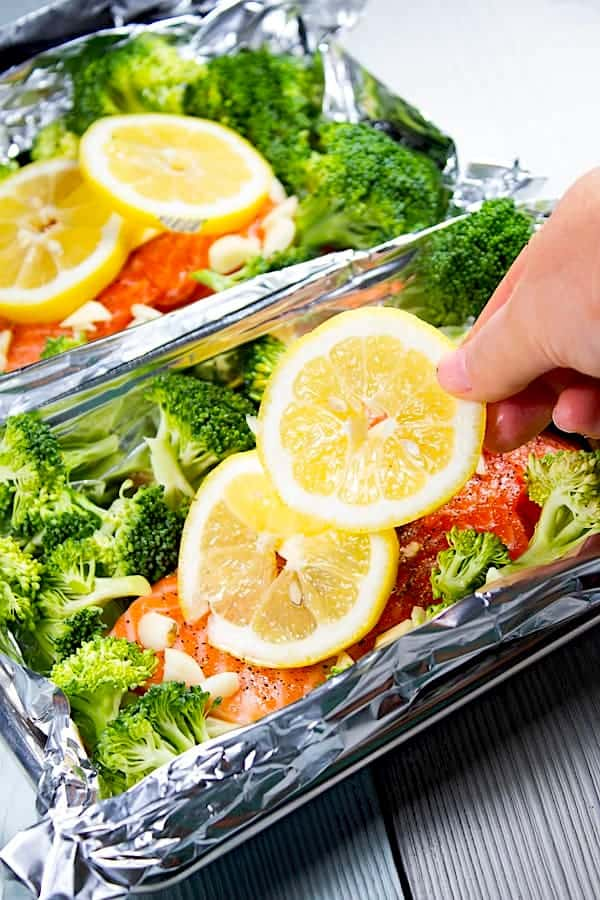 adding lemon to salmon with broccoli in foil pouch