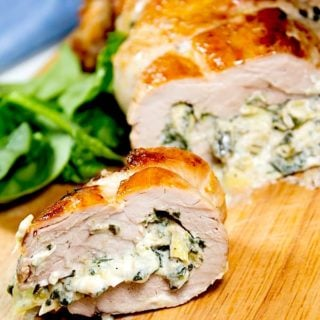 spinach artichoke stuffed pork tenderloin with slice cut on cutting board