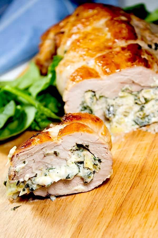 spinach artichoke stuffed pork tenderloin with slice cut on cutting board