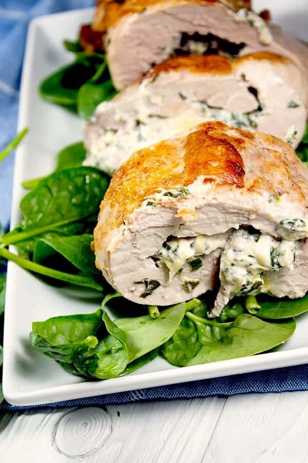 spinach stuffed pork tenderloin on platter with spinach