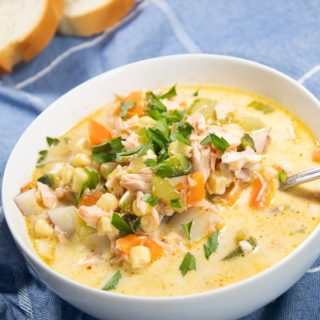 A white bowl full of salmon corn chowder