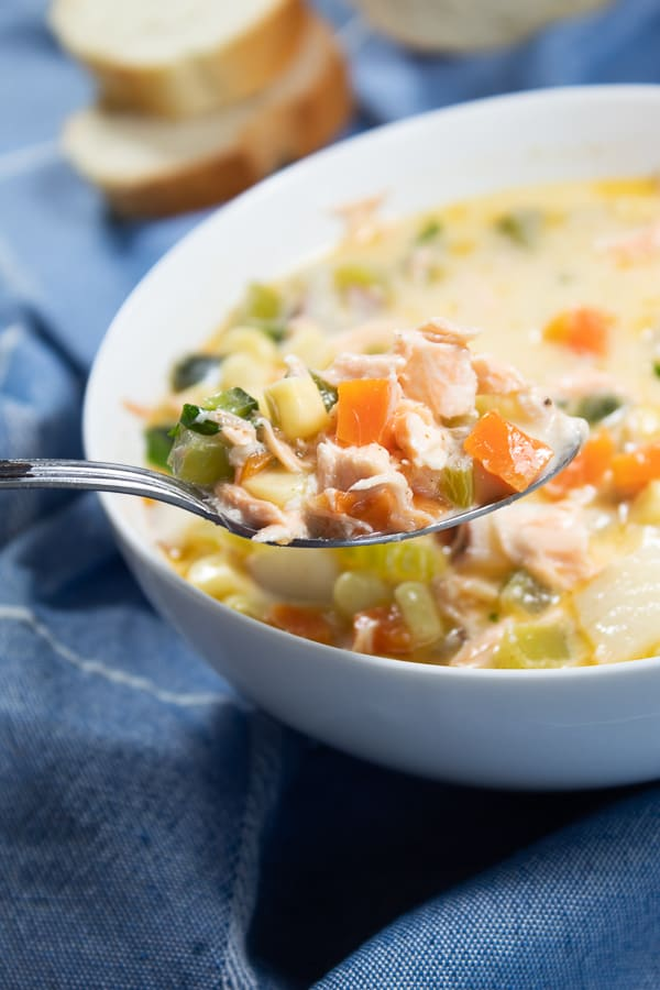 A white ceramic bowl full of summer salmon and corn chowder