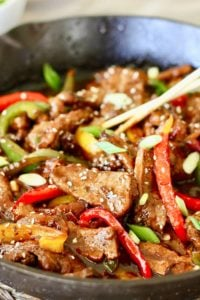mongolian beef with peppers in skillet with chopsticks