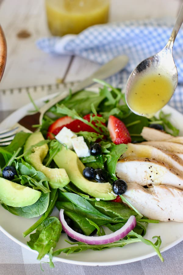 grilled chicken with strawberry spinach salad on a white plate