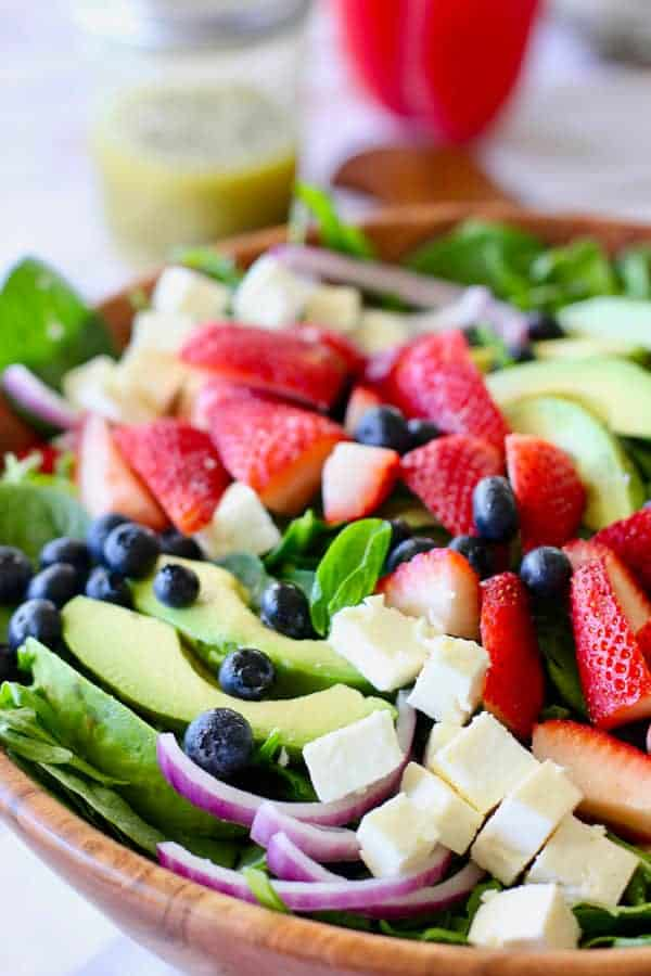 strawberry salad ingredients in a large wooden bowl