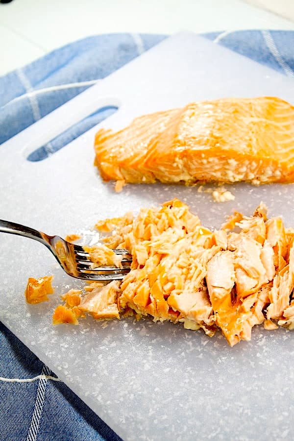 flaking salmon with a fork on a white cutting board